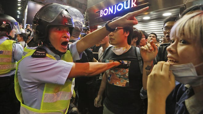 Police officers stop the protesters blocking the road after police cleared barricades and tents in Mong Kok district of Hong Kong, Wednesday.