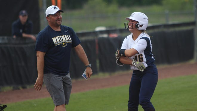 Whitnall head coach Tom Hickman (left) and junior pitcher Haley Wynn stand near third base after a triple by Wynn during a state semifinal game.
