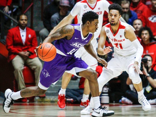 Abilene Christian's Isaiah Tripp (10) drives as New Mexico's Anthony Mathis (31) and Dane Kuiper, center, defend during the first half in Albuquerque, N.M., Wednesday, Nov. 30, 2016.