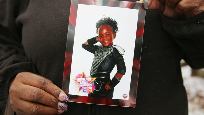 An aunt holds a photo of 7-year-old Chanell Berry, who was shot and killed around 8:30 p.m. Sunday in her home on Steel in northeast Detroit as she played with her Christmas presents.