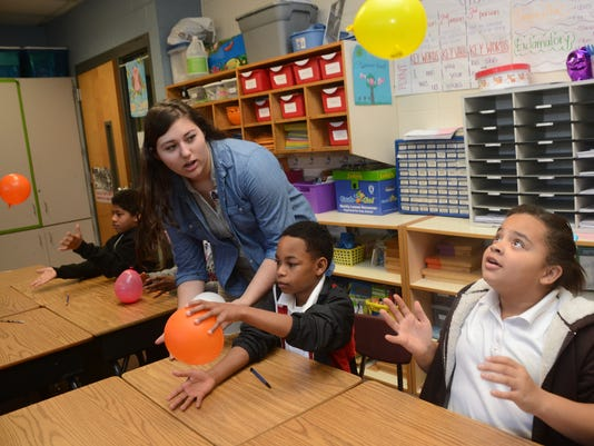ANI Pineville students teach Rosenthal students Michaela Davis (far left), a junior at Pineville High School and a member of the Pineville High Science Club, helps Rosenthal Montessori fourth-graders Eric Jones and Alyssa Hammond with a science experiment