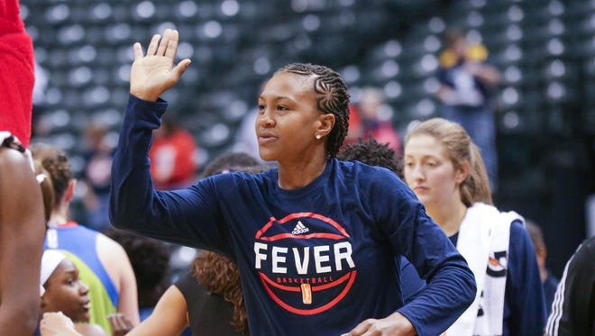 The Indiana Fever's Tamika Catchings high-fives Freddie Fever after a preseason game against the Dallas Wings on  Sunday, May 1, 2016, at  Banker's Life Fieldhouse.