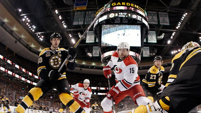 In this photo taken with a fisheye lens, Boston Bruins' Zdeno Chara, left, and Carolina Hurricanes' Tuomo Ruutu (15) eye a loose puck in front of Boston Bruins goalie Chad Johnson during the third period of the Bruins' 3-2 overtime win in an NHL hockey game in Boston Saturday, Nov. 23, 2013.