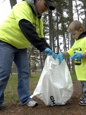 Volunteers Season Schmitz, left, and her 4-year-old son Isaac, both of Ringle, pick trash during the 2010 Ghidorzi's Green and Clean at Marathon Park.