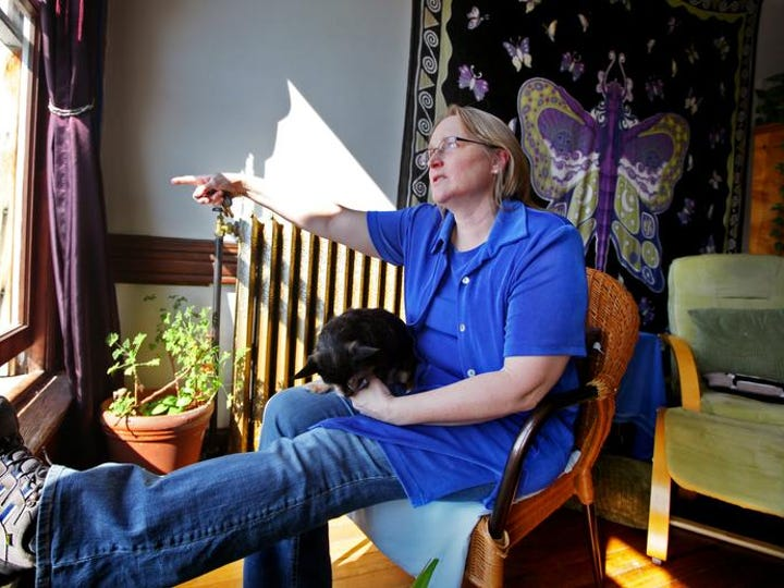 Karen Lawrence admires her view with Daisy, from her top floor apartment on Beverley Street on Thursday, March 6, 2014. The oversized windows offer a 180 degree view of downtown Staunton.