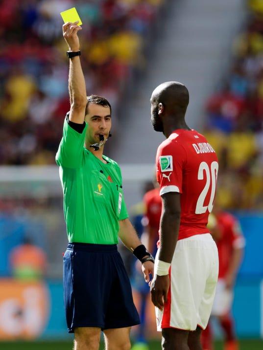 Switzerland's Johan Djourou is given a yellow card by referee Ravshan Irmatov from Uzbekistan during the group E World Cup soccer match between Switzerland and Ecuador at the Estadio Nacional in Brasilia, Brazil, Sunday, June 15, 2014.  (AP Photo/Fernando Llano)