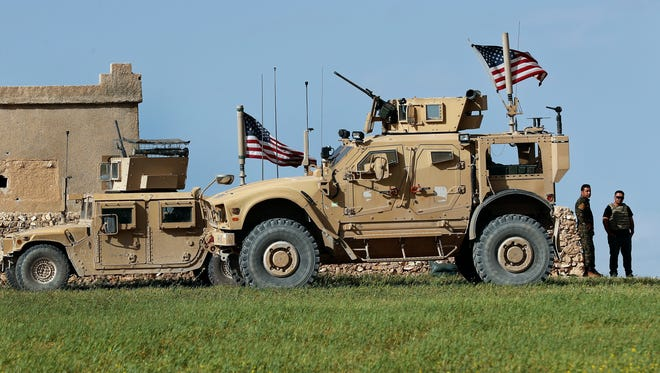 A fighter, second from right, of U.S-backed Syrian Manbij Military Council stands next to a U.S. humvee at a U.S. outpost near a road leading to the tense frontline between Syrian Manbij Military Council fighters and Turkish-backed fighters, at Halawanji village, north of Manbij town, Syria.