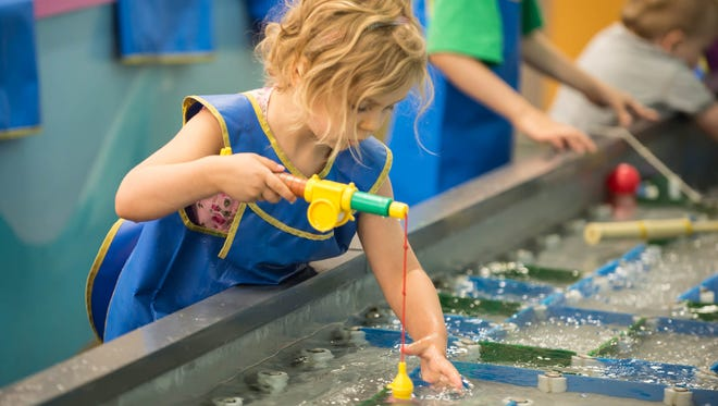 """In this 2015 photo, Daphne Willis of Battle Creek tries to catch a play fish at Kids 'N' Stuff in downtown Albion. Four year old Daphine Willis from Battle Creek tries to catch a play fish at Kids """"N"""" Stuff in downtown Albion."""