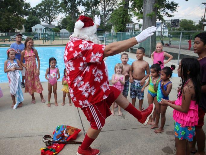 Santa, portrayed by Raritan Borough assistant recreation director Bob Andreychak, visits children at the Frelinghuysen Park Pool to celebrate Christmas in July, Thursday, July 31, 2014, in Raritan Borough, NJ.  Photo by Jason Towlen