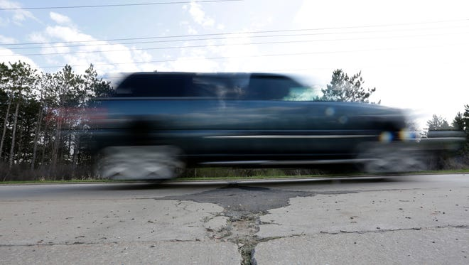 A car bumps along some recently repaired potholes on West 29th Street in Marshfield on Thursday, April 21, 2016.