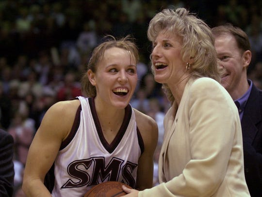 Coach Cheryl Burnett presents Jackie Stiles with the game ball during a postgame ceremony after Stiles set the NCAA career scoring record in 2001.