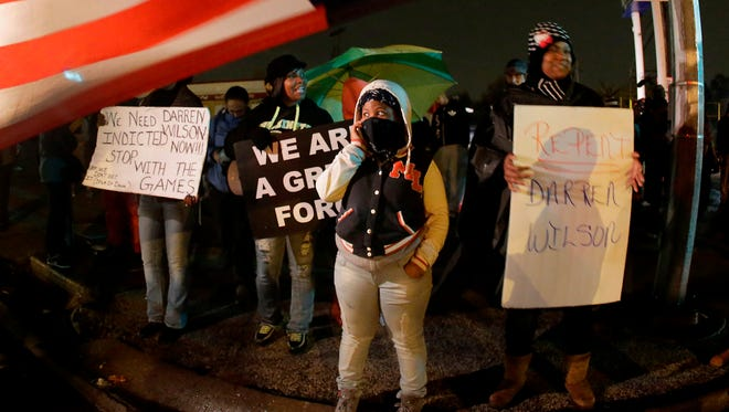 Protesters on Nov. 22 hold signs along a stretch of road where violent protests occurred following the August shooting of an unarmed black teenager by a white police officer in Ferguson, Mo.