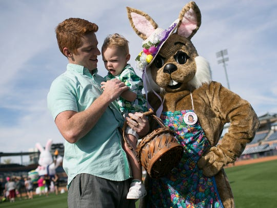 Bradley Dawson (left) holds his two-year-old son Alister Dawson (center) for a photo with Mrs. Easter Bunny at the 42nd annual Dolly Sanchez Memorial Easter Egg Hunt at the Peoria Sports Complex on March 31, 2018, in Peoria.