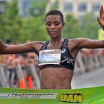 Diane Nukuri Johnson, of Iowa City, at the finish line to take first place in the Dam To Dam half marathon women's race in downtown Des Moines on Saturday morning May 31, 2014.