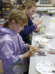 Malia Hall (front) and Carolyn Davis take part in Family Clay Sunday at the Willamette Art Center in 2012.