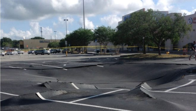 The parking lot at a Publix grocery store near Legoland in Winter Haven is buckling and dipping because of a suspected sinkhole.