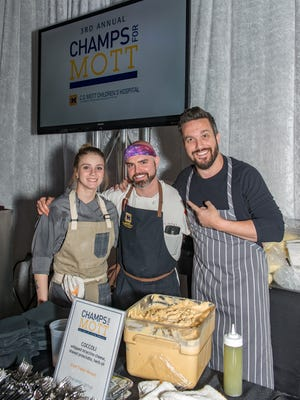 The CHAMPS for Mott Culinary Gala showcases the flavors of Michigan's buzzy food scene. Beneath the dramatically soaring ceilings of the Delta Air Lines hangar at DTW, food lovers will get a taste for each corner of the Great Lakes State. From left, Ciara Ball and Chef Joe VanWagner of Local Kitchen and Bar, and celebrity chef Fabio Viviani.