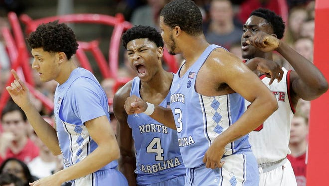 North Carolina's Isaiah Hicks (4) reacts with Justin Jackson, left, and Kennedy Meeks following Hicks' basket as North Carolina State's Abdul-Malik Abu watches at rear during the first half of an NCAA college basketball game in Raleigh, N.C., Wednesday, Feb. 15, 2017. North Carolina won, 97-73.