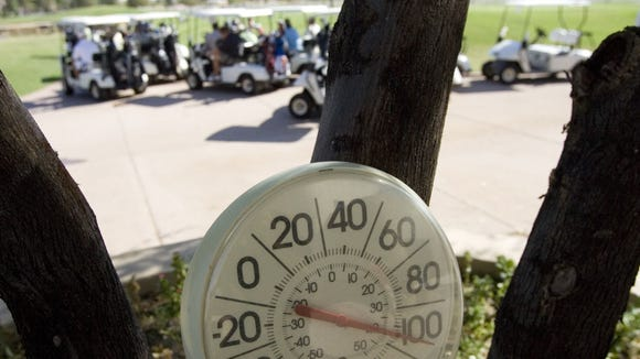 145788 6/17/07- Golfers get into their golf carts as a nearby thermometer warns of the hot weather during a golf tournament Tuesday at Western Skies Golf Course. (Pat Shannahan/ The Arizona Republic)