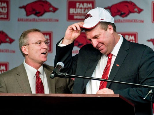 FILE - In this Dec. 5, 2012, file photo, Arkansas athletic director Jeff Long, left, presents Bret Bielema with a cap as Bielema is introduced as the school's new head coach during an NCAA college football news conference in Fayetteville, Ark. Arkansas has announced the firing of athletic director Jeff Long, Wednesday, Nov. 15, 2017, after nearly 10 years at the school. His firing comes at a time of turmoil for the Arkansas football program, which is 29-32 in five seasons under coach Bret Bielema _ including a mark of 11-27 in the Southeastern Conference. (AP Photo/April L. Brown, File)