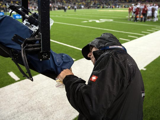 In this 2015 file photo, a member of the ESPN crew cleans off the lens of the spider camera during the first half of the game between Baylor and Oklahoma. On-campus production upgrades in C-USA will allow member schools to produce their own games.