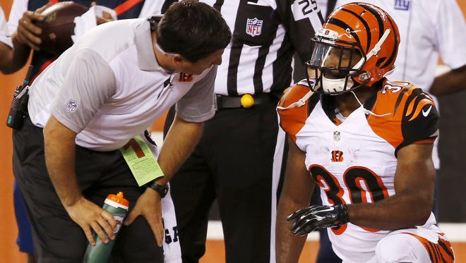 Cincinnati Bengals running back Cedric Peerman (30) is checked by a trainer after slowing getting up from a hard hit during the preseason NFL game between the New York Giants and the Cincinnati Bengals, Friday, Aug. 14, 2015, at Paul Brown Stadium in Cincinnati, Ohio.