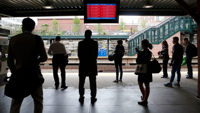 Commuters wait for a delayed New York City-bound train on Friday at the New Rochelle station. New Haven Line trains are restored and operating close to schedule after wire repairs in Greenwich, Connecticut, delayed trains up to 60 minutes from Harrison to Grand Central.