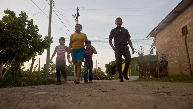In this Saturday, July 19, 2014 photo, deportee Elsa Ramirez, 27, walks with her children Sandra, 8, Cesar Ramos, 5, and her brother Elvin Ramirez to a nearby church in Tocoa, Honduras. The migration flood to the US-Mexico border began earlier this year after word circulated that children, and women with children, would be released in the U.S pending immigration hearings, which could be delayed for years due to a backlog.