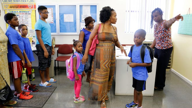 Youth director Sonia Barton, right, instructs  Jasmine Metellus where to take her kids Kayla Jean-Mary, 6, and Karl Jean-Mary, 7, after they registered for the village of Spring Valley summer camp, Aug. 6, 2014, at Louis Kurtz Civic Center in Spring Valley. This is the first day of camp following Mayor Demeza Delhomme's release from jail. Delhomme spent four days in jail over the conflict involving the camp.