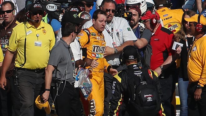 Kyle Busch, driver of the #18 M&M's Toyota, is escorted away by a NASCAR official after an incident on pit road with Joey Logano (not pictured), driver of the #22 Pennzoil Ford, following the Monster Energy NASCAR Cup Series Kobalt 400 at Las Vegas Motor Speedway on March 12, 2017 in Las Vegas, Nevada.