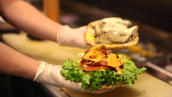 Melina Sippel prepares the TKB chicken breast club sandwich, made with sliced chicken breast, bacon, avocado and dressing.