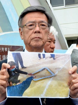Okinawa Gov. Takeshi Onaga, holds a picture of a metal window frame fallen from U.S. military aircraft CH-53 outside an elementary school in Ginowan, Okinawa Wednesday, Dec. 13, 2017.