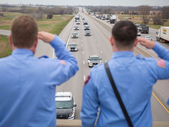 Grimes firemen salute on the 86th Street overpass over