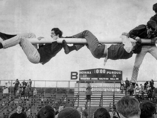 Indiana University football fans climb on one of the