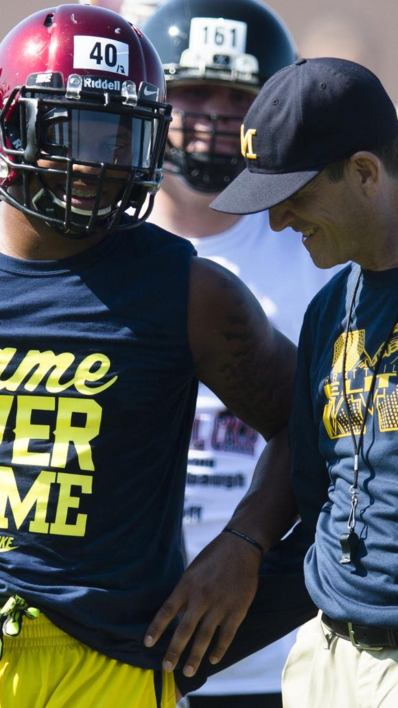 Michigan Head Coach Jim Harbaugh talks to Prattville's Kingston Davis during Coach Jim Harbaugh's Elite Summer Football Camp at Prattville High School in Prattville, Ala., on Friday, June 5, 2015.