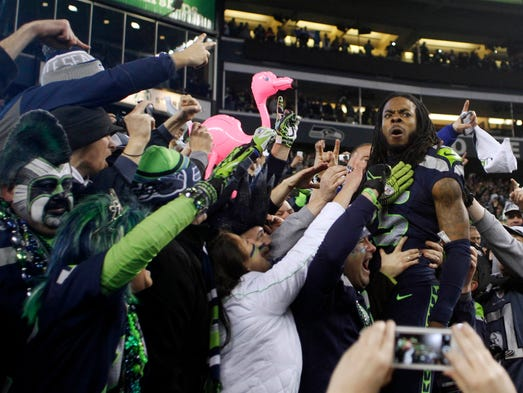 Seattle Seahawks cornerback Richard Sherman (25) celebrates with fans in the stands after the 2013 NFC Championship football game against the San Francisco 49ers at CenturyLink Field.