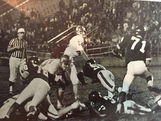 Taken from a yearbook photo, this shot depicts Jim Warren passing the ball in his senior season as Fairfield's quarterback and team captain.