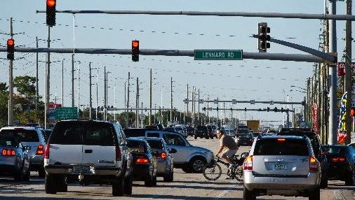 A bicyclist rides across U.S. 1 as traffic moving north stops at a red light headed into Port St. Lucie, past Lennard Road approaching Port St. Lucie Boulevard on Jan. 28, 2015.