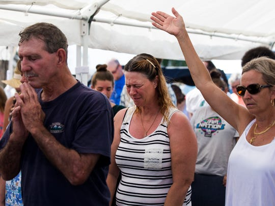 """Residents of Chokoloskee pray together during a service at Chokoloskee Church of God on Sunday, Sept. 17, 2017. The Rev. Lynnette Morris, who preached in white crabber boots, told the crowd that """"not only are you swamp tough, but you're Jesus tough."""""""