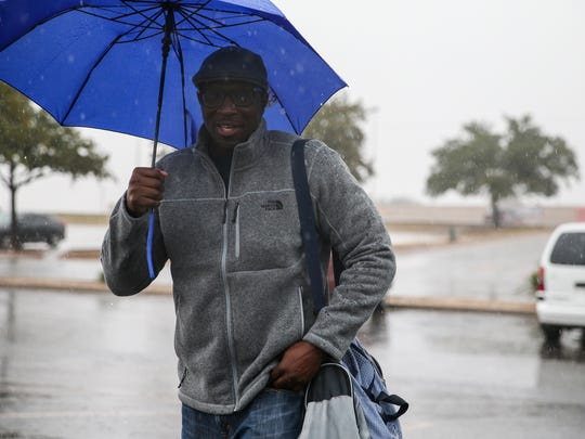 George Adam walks across a parking lot during a rainstorm Wednesday, Nov. 8, by Sunset Mall in San Angelo.