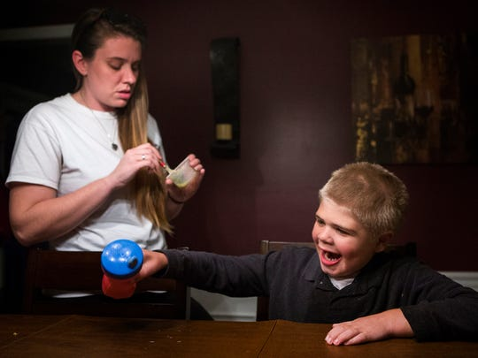 Sharon Rapposelli, a home health aid for the Kapes family, stirs a bowl of yogurt mixed with supplements for eight year-old Brayden Kapes as Brayden laughs at an episode of the Backyardigans on a nearby iPad at the Kapes home in Wilmington on Wednesday afternoon, October 26, 2016.