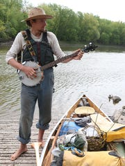 Ben Hoksch plays a banjo on the bank of the river Monday