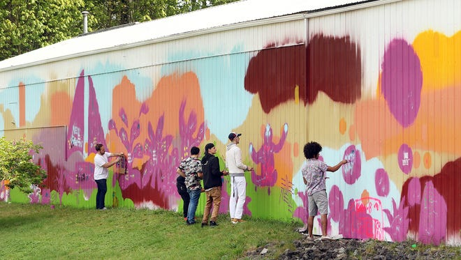 Community members paint at a mural taking shape on the side of the city's Public Works building. The site is proposed for the future Poulsbo Skate Park. The community is invited on Saturday to help paint the mural.