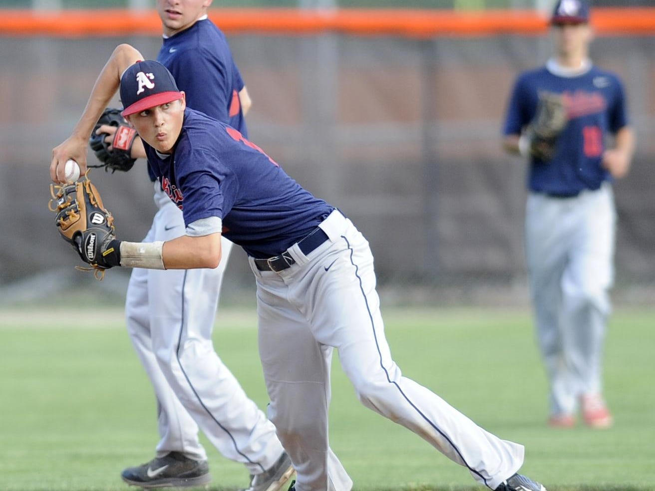 Licking County 17U Athletics shortstop Cody Dennis throws to first after fielding a ground ball during a game earlier this summer. The A's have played a top-notch schedule to increase exposure for their players.