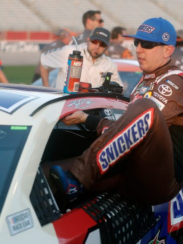 Kyle Busch gets out of his No. 18 Toyota after winning