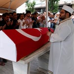 Relatives of Siddik Turgan, a custom officer at Ataturk Airport, who was killed in the attacks on June 28, 2016, pray in front of his coffin during a funeral in Istanbul on June 29, 2016.