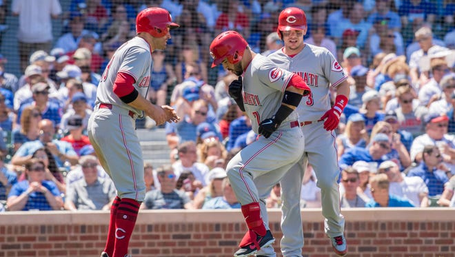 Cincinnati Reds third baseman Eugenio Suarez (center) celebrates his three run home run with first baseman Joey Votto (left) and second baseman Scooter Gennett (right) during the third inning against the Chicago Cubs at Wrigley Field.