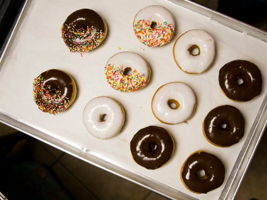 Trackside Donuts & Cafe co-owner Susie Alansky begins to frost, glaze and fill various doughnuts for the early morning rush Tuesday, May 22, 2018, in Bonita Springs.