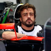 Fernando Alonso sits in his car in the McLaren team