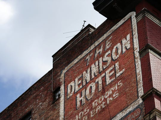 A sign on the side of the Dennison Hotel